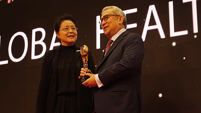 IMPROVING GLOBAL HEALTH. Ernesto Garilao receives the Impact in Global Health Award from Ms. Liang Weina, Vice-chair of ChinaInstitute of Strategy and Management. Photo courtesy of Zuellig Family Foundation