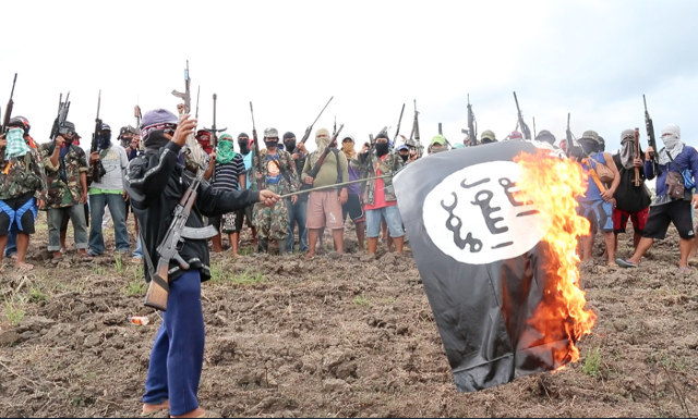 RED GOD'S SOLDIERS. Members of armed Christian group Red God's Solders set on fire a flag of ISIS during a gathering Tuesday, January 19, 2016 somewhere in Central Mindanao mountains. Photo by Jef Maitem.