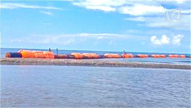 CHINESE-MARKED BUOYS. Fishermen in Zambales remove these markers seen to assert China's claim over the West Philippine Sea. Screen grab from Rappler video