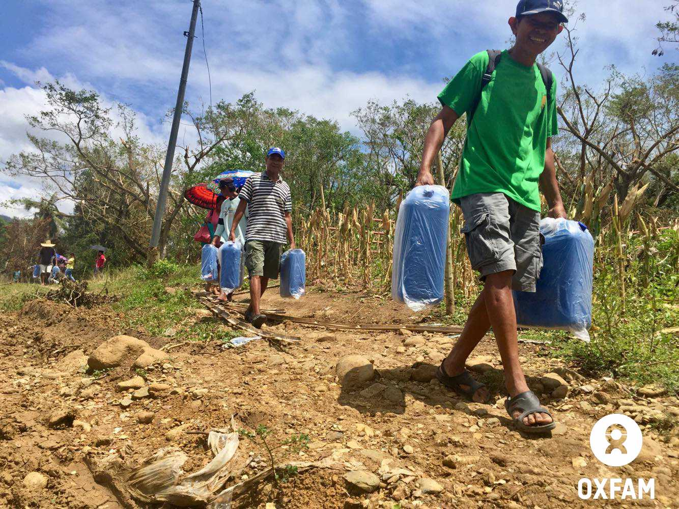Locals of Rizal town led by its officials helped in carrying water supplies for two remote communities. Photo by April Bulanadi/Oxfam