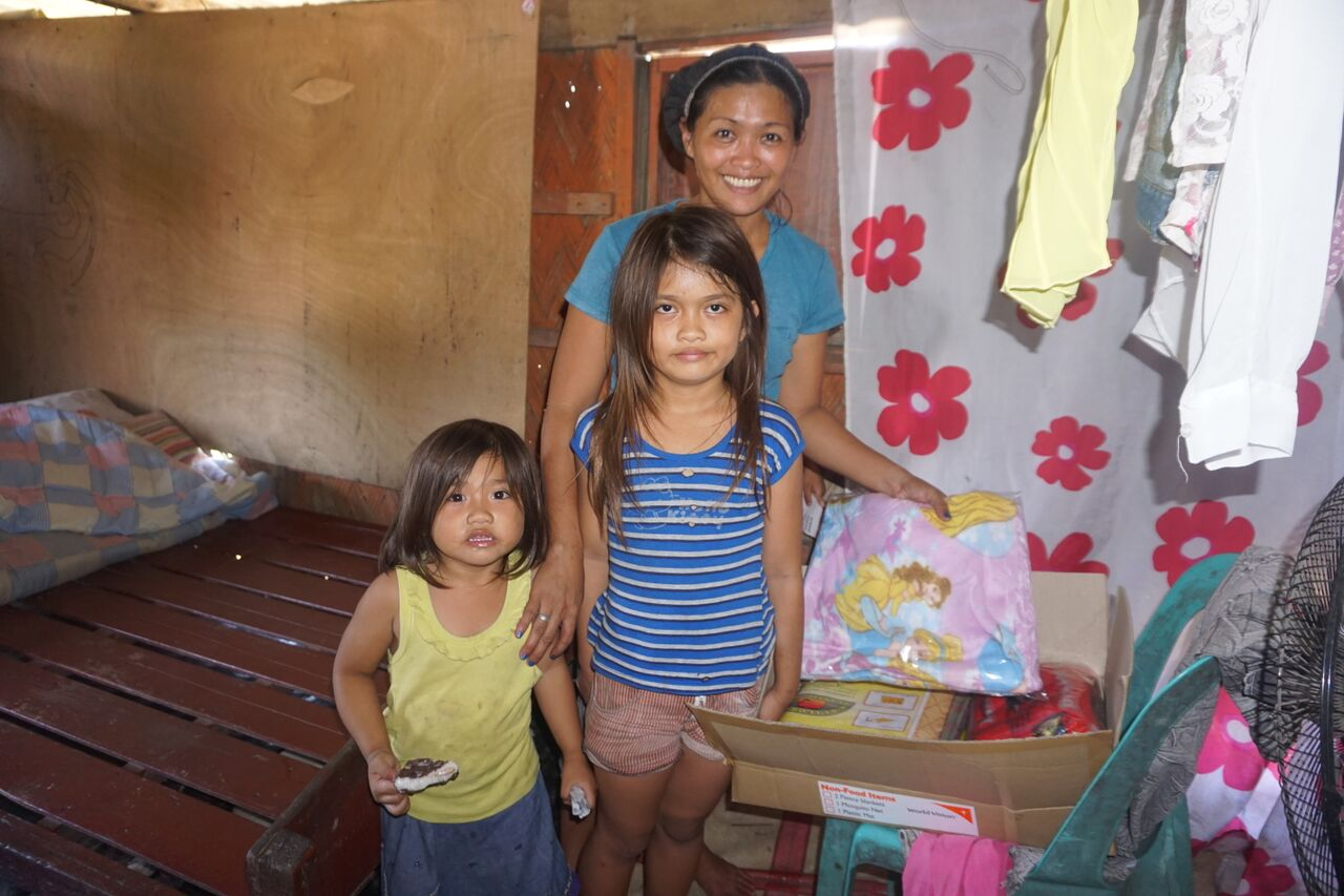 Kristine and her two children check out relief goods from boxes given by World Vision Philippines. They say the help will be useful as they try to rebuild their homes. Most houses in their barangay were destroyed by heavy rains and floods from Typhoon Lando. Photo courtesy of World Vision