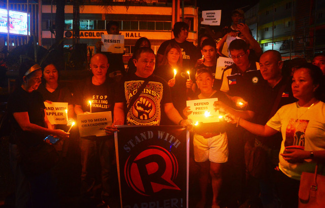 LIGHT IN THE DARK. In this photo taken on Friday, January 19, members of the press and other organizations light candles to call for press freedom at the Fountain of Justice in Bacolod City. Photo courtesy of NUJP-Bacolod