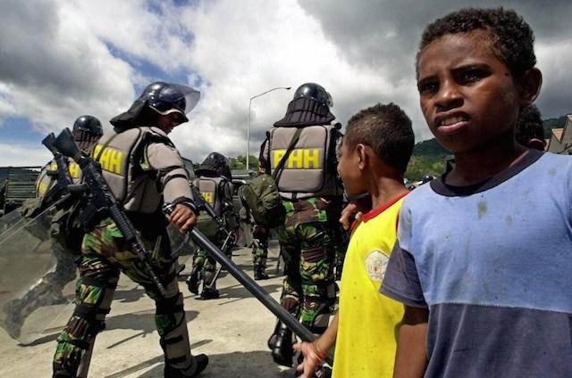 Warga Papua menyaksikan aparat Kepolisian bersiap mengantisipasi kerusuhan di foto ini yang diambil pada tahun 2000. Foto oleh AFP