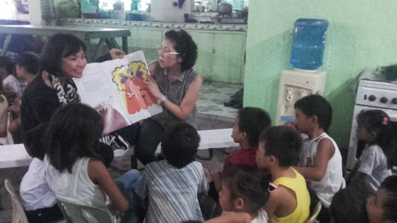 LIBRARY. Volunteers of LRP read a storytelling book to the kids. All photos by Dwight Angelo de Leon