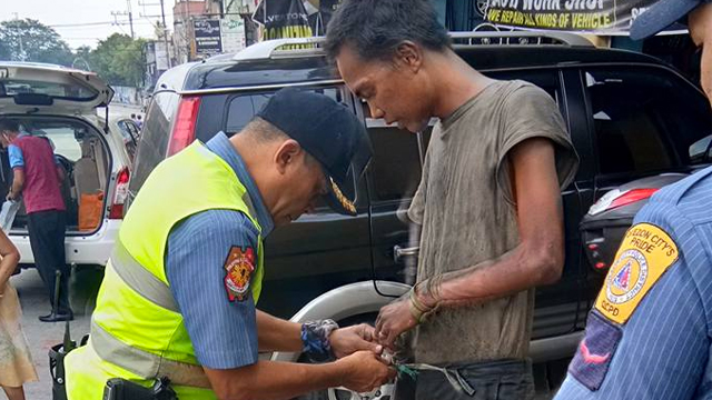 CARE. PCI Edwardo Bea dressing up the homeless man he saw in Libis, Quezon City while setting up a checkpoint.
