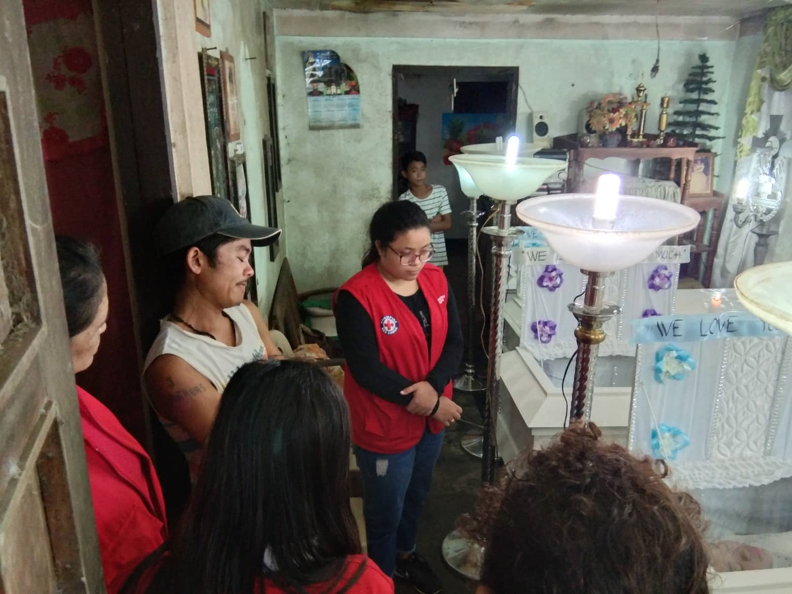 ASSISTANCE. Members of the Philippine Red Cross - Camarines Sur provide a psychosocial service briefing to Benjie de Lima of San Vicente in Baao town, who lost his wife and 4 children on Sunday. Photo courtesy of Philippine Red Cross-CamSur