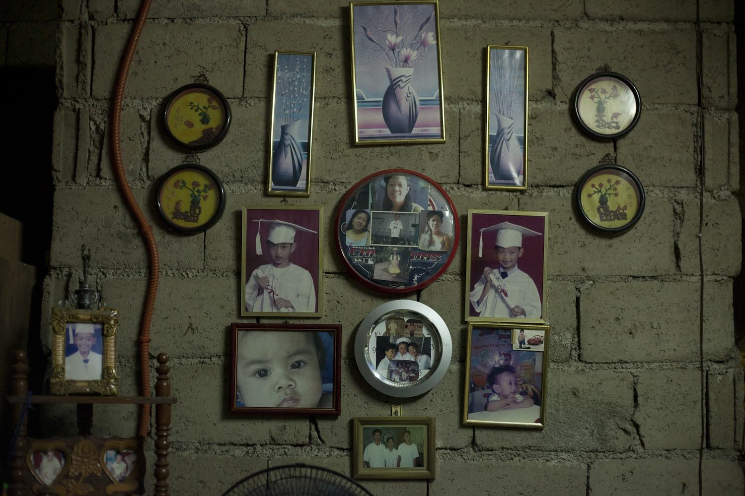 FAMILY PICTURES. Pictures of overseas Filipino worker Norma Brion and her children Jim and Joy hang on the wall of their home. Photo by Geric Cruz