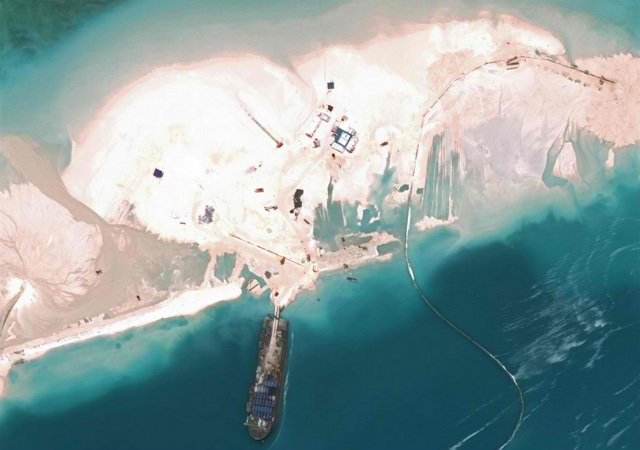 This satellite image shows Sand Cay, the 9th largest island in the Spratlys, as of March 16, 2015. Photo by CSIS Asia Maritime Transparency Initiative/DigitalGlobe Photo by CSIS Asia Maritime Transparency Initiative/DigitalGlobe