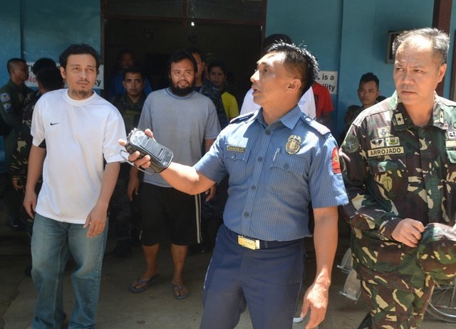 FREE. Rescued Philippine coast guard worker Gringo Villaruz (L) and Alan Pagaling (2nd L-behind, with beard) are escorted out of the hospital after they were rescued from Al-Qaeda militants, in the town of Jolo on the Philippine southern island of Mindanao on August 20, 2015. AFP PHOTO