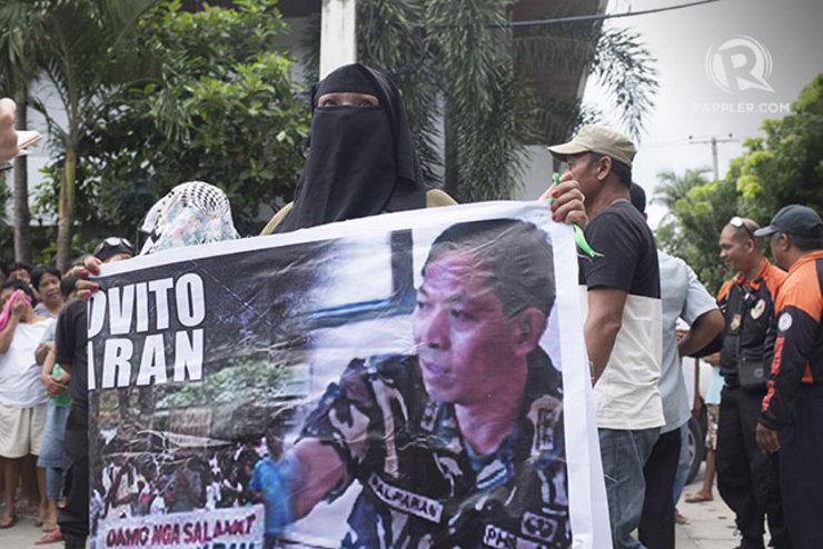 A pro-Palparan protester holds a poster of the former general accused of human rights violations in a protest at the Bulacan Regional Trial Court, 1 September 2014. Photo by Carlo Gabuco