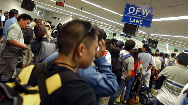 COMING HOME. OFWs line up at the airport, eager to come home. AFP file photo