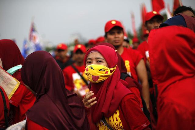 BURUH. Seorang pekerja Indonesia menggunakan masker pikachu dalam demonstrasi Hari Buruh Internasional di depan Istana Negara, 1 Mei 2014. Foto oleh Mast Irham/EPA