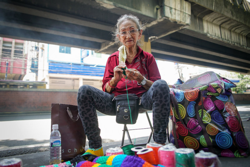 STANDOUT. Nanay Ely, with her colorful crochet products, stands out under the LRT1 line in Tayuman, Manila. All photos by Vee Salazar/Rappler