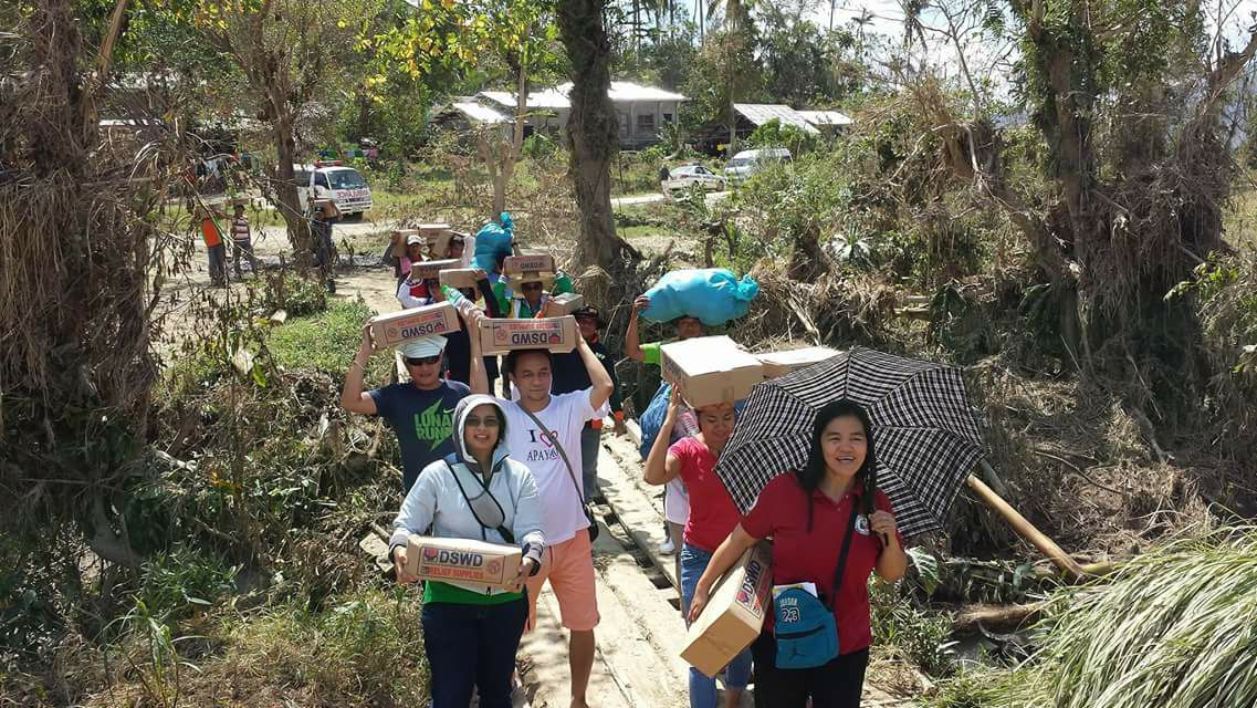 BY FOOT. DSWD social workers and volunteers bring boxes of relief supplies to a remote village in Apayao province in Cordillera by foot.
