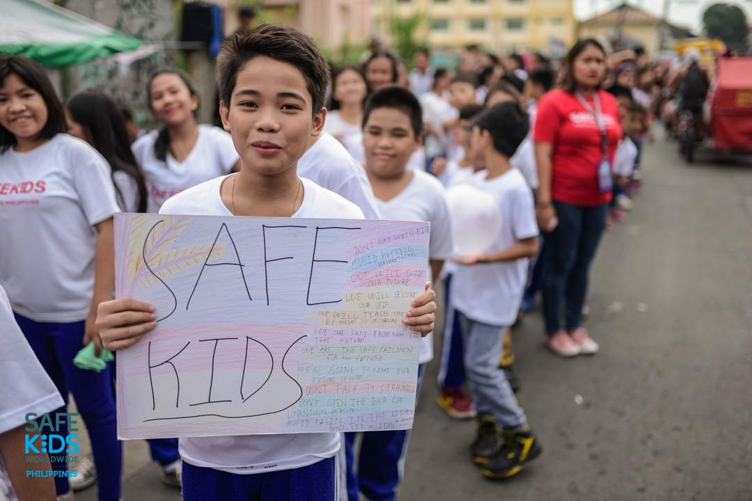 PARADE. An elementary student holds a sign that lists the things children must do and avoid to remain safe. Photo by Heinz Reimann Orais