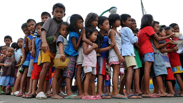 Filipino children line up in a feeding program. File photo by Jay Directo/AFP