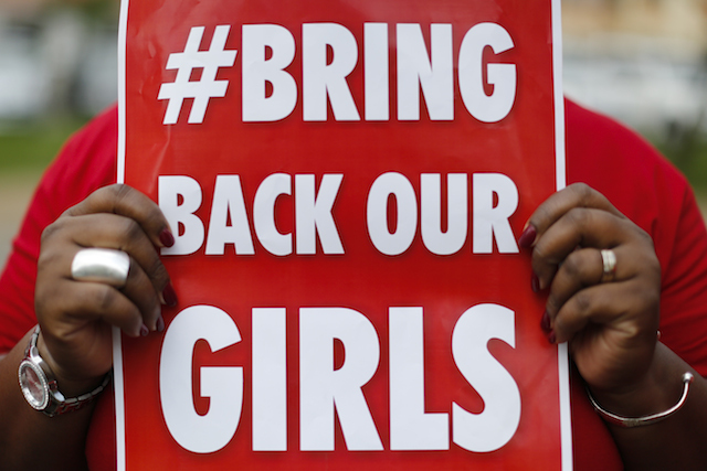 MISSING GIRLS. A Nigerian woman holds a placard in front of the Nigerian High Commission during a protest against the kidnapping of the Nigerian school girls. Dai Kurokawa/EPA