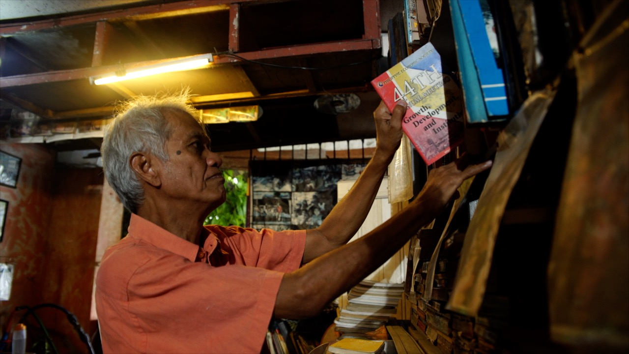 24/7 LIBRARY. Mang Nanie fixes the books in the shelf before library visitors arrive in his house in Makati City
