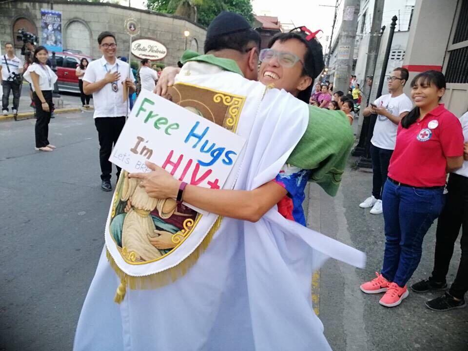 ACCEPTANCE. A Catholic priest hugs a person with HIV at the Grand Marian Procession in Intramuros, Manila. Photo Courtesy of Manila Red Cross Youth