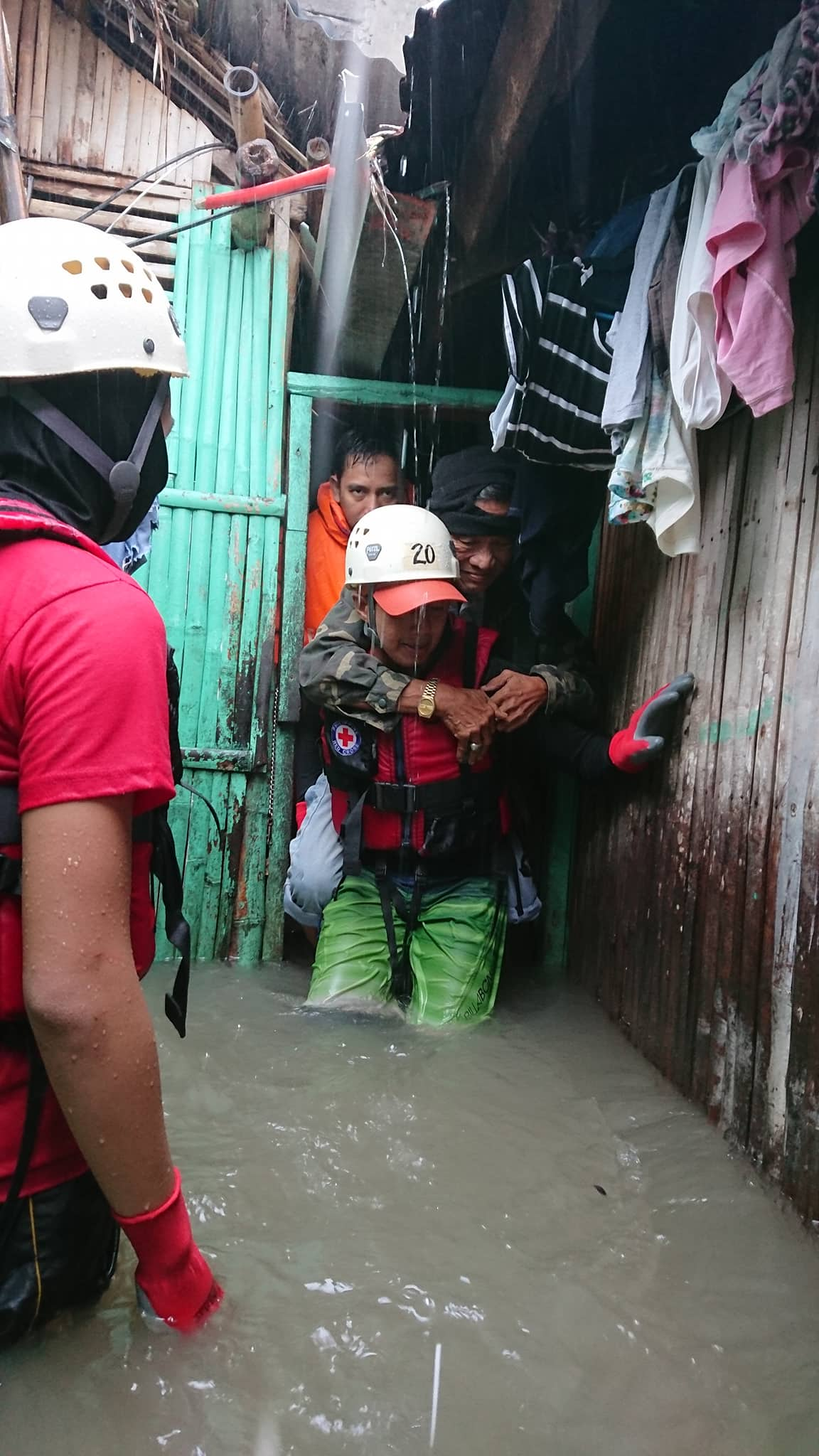 RESCUE. A disaster responder carries an old man amid a knee-level flood. Photo courtesy of Philippine Red Cross - Camarines Sur