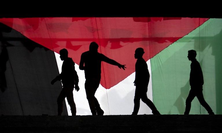 PALESTINA. Pemuda Palestina sedang melintasi bendera nasional mereka di kota Gaza, 7 Desember, 2013. Mahmud Hams/AFP