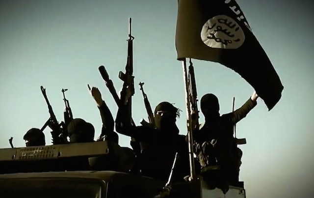 An image grab taken from a propaganda video released on March 17, 2014 by the Islamic State of Iraq and Syria (ISIS)'s al-Furqan Media allegedly shows ISIS fighters raising their weapons as they stand on a vehicle mounted with the trademark Jihadists flag at an undisclosed location in the Anbar province. File Photo by Al-Furqan Media/AFP