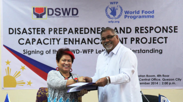 DSWD Secretary Corazon Juliano-Soliman and World Food Program Country Director Praveen Agrawal exchange documents during the Signing Ceremony for the Letter of Understanding between the DSWD and the UN-WFP on Disaster Preparedness and Response Capacity Enhancement Project.