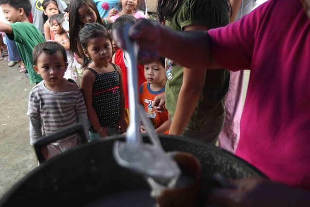 SATIATING HUNGER. Children wait their turn at a feeding program for informal settlers in Quezon City. File photo by Rolex dela Peña/ EPA