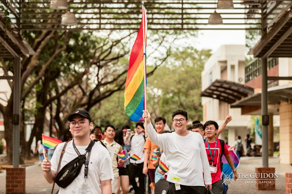 """Sanggunian Gender Equality Co-Commissioner Ramon Tanjuatco, holding the rainbow banner, leads the band of Ateneans on the """"One Big Pride"""" march on March 15, 2019. Photo by Zach G. Garcia/The GUIDON"""