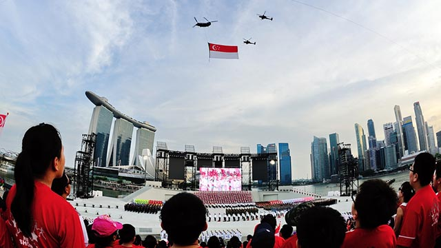 POMP AND CIRCUMSTANCE. Singaporeans watch helicopters holding up the national flag on Singapore National Day.