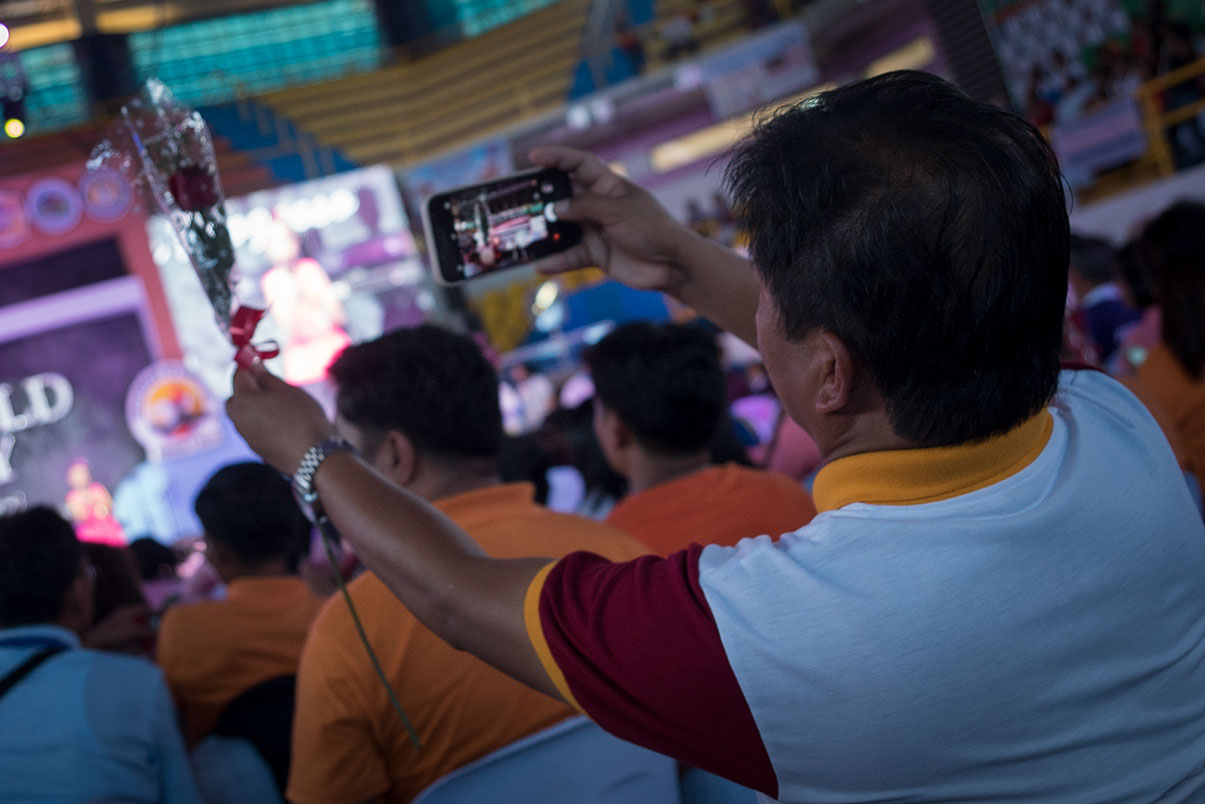 TRIBUTE. A teacher takes a photo of a rose handed to him by the Department of Education at the celebration