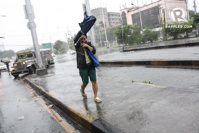 GLENDA'S WRATH. A commuter braves rain and winds caused Typhoon Glenda in Quezon City. File photo by Manman Dejeto/Rappler