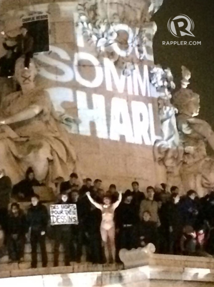 A naked woman leads a chant during a protest protest vigil for the victims of the attack on the French magazine Charlie Hebdo, at the Place de la Republique in Paris, France, January 7, 2014. The projected text behind the protesters read, 'We Are Charlie.' Ryan Songalia/Rappler