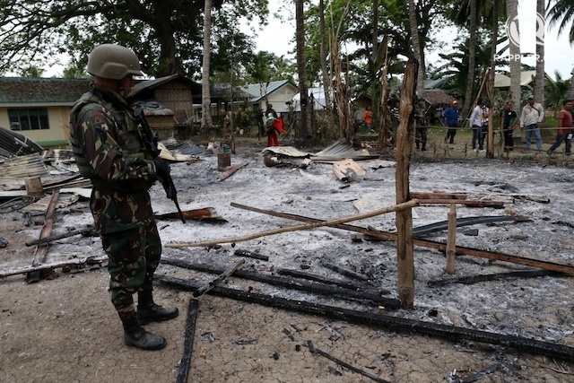 ATTACK. In this file photo, an Army officer  stands beside a house set on fire by the Bangsamoro Islamic Freedom Fighters in central Mindanao as fierce gun battles continue. File photo by Jeoffrey Maitem/Rappler