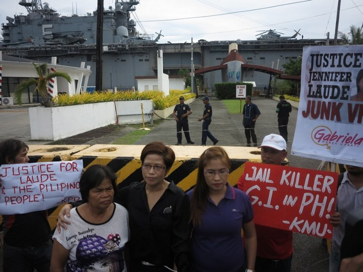 Relatives of murdered Filipino transgender woman Jennifer Laude, including her mother Julita Laude (L), stand in front of the port gate where USS Peleliu (back) is docked at Subic, October 18, 2014, to bring a notice to the murder suspect Private First Class Joseph Scott Pemberton who is detained onboard the ship. Robert Gonzaga/AFP