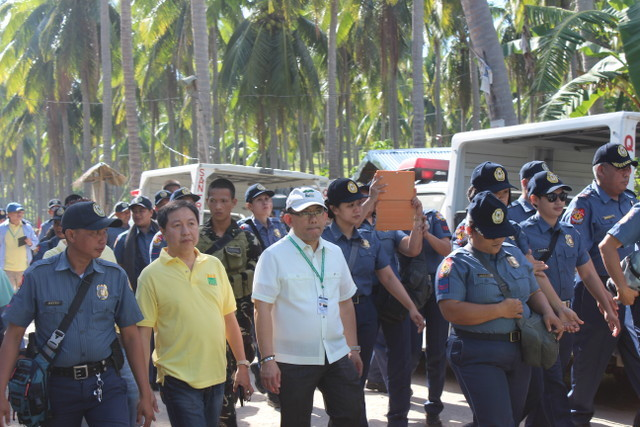 FUTILE PLAN. DAR Undersecretary for Legal Affairs Luis Pangulayan (in white) and police personnel accompany farmers during an installation attempt on May 15, 2015