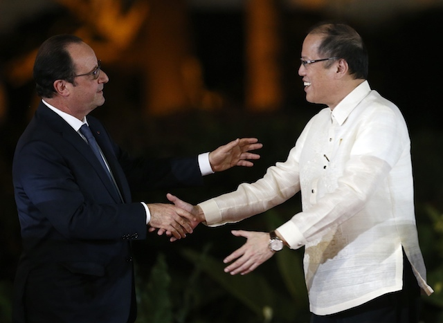 COOPERATION. President Benigno Aquino III and French President Francois Hollande shake hands after witnessing the signing of various agreements between their countries. Photo by Dennis Sabangan/EPA