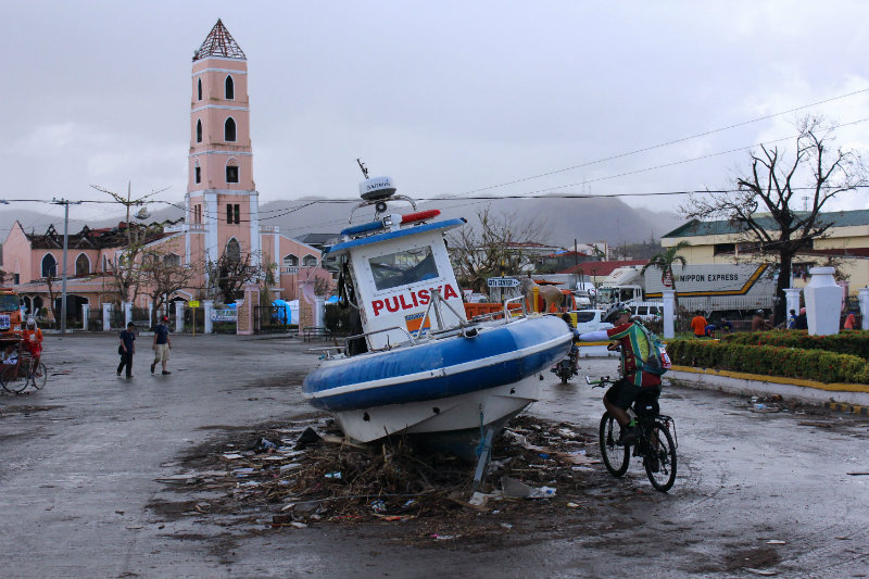 DEBRIS EVERYWHERE. Parts of houses, cars, and even boats litter the streets in the aftermath of Yolanda