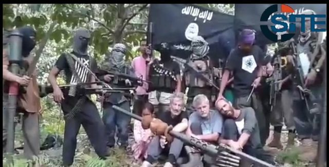 TERROR GROUP. Members of the Abu Sayyaf pose with hostages, two of whom they have already killed.