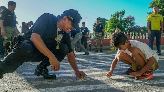 NEW SIGHT. Students help a Cagayan Highway Patrol Group officer to draw a pedestrian lane in front of their school. Photo by Vee Salazar/Rappler