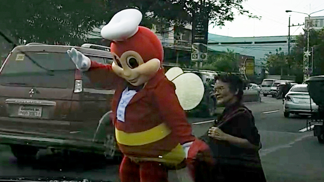 A screen grab of the viral video of Jollibee helping an old lady cross the street.