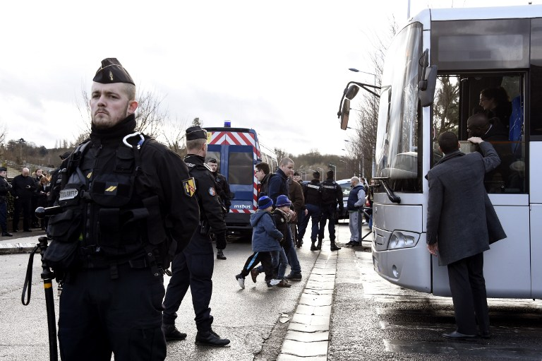 TO SAFETY. French gendarmes stand by as children are evacuated from a school in Dammartin-en-Goele, north-east of Paris, where two brothers suspected of slaughtering 12 people in an Islamist attack on French satirical newspaper Charlie Hebdo held one person hostage as police cornered the gunmen, on January 9, 2015. Dominique Faget/AFP