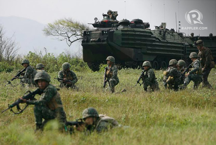 JOINT EXERCISE. Filipino troops position themselves near a marine amphibious assault vehicle manned by their US counterparts during a mechanized assault exercise as part of the 2014 Amphibious Landing Exercise (PHIBLEX) at the Naval Education and Training Command (NETC) in Zambales on Sunday. Around 1,000 Filipino and 3,000 US marines and sailors will join the annual joint military exercise that will last for 12 days. Photo by Ben Nabong/Rappler