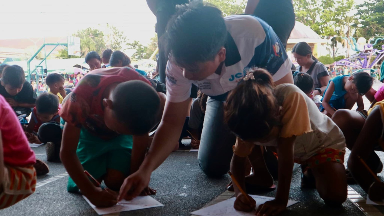 MORE THAN GIFTS. A volunteer in Lingayen, Pangasinan assists kids in writing during an outreach event at the plaza. Photo courtesy of Jerico Samson