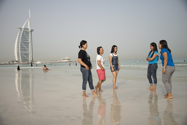 RESPITE. Filipino workers take a breather at a Dubai beach, with the landmark Burj Al Arab in the background. Photo by Jo Kearney