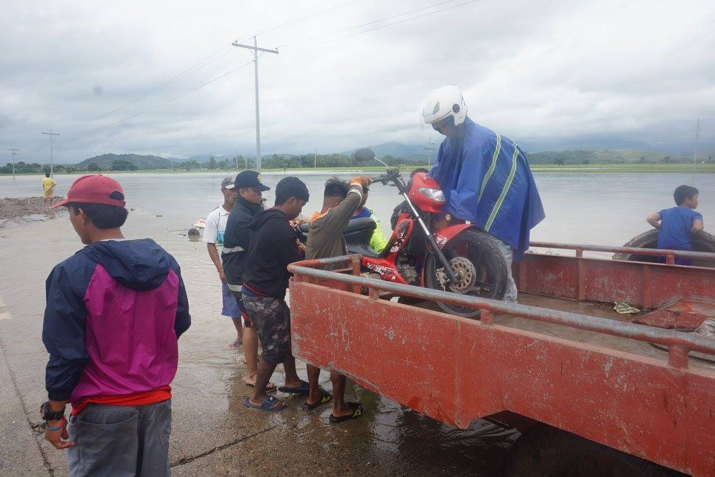HITCH. A motorcycle is placed on the back of  a truck to help the rider and his vehicle cross the Pola spillway