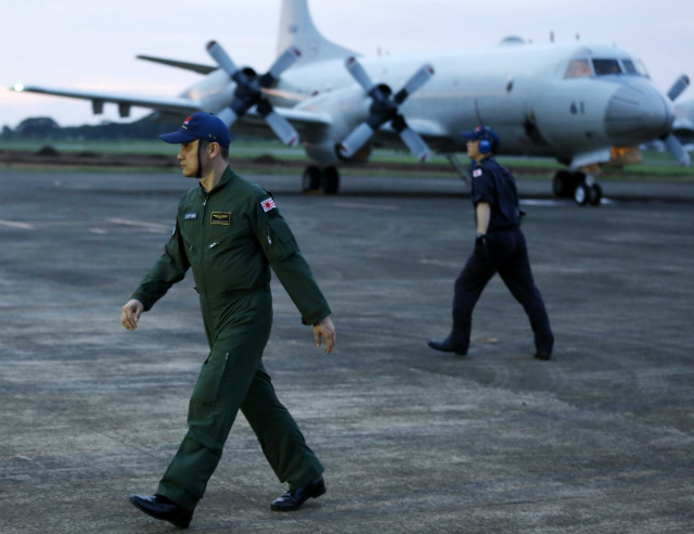 PHILIPPINES' ALLIES. Japanese Maritime Self-Defense Force personnel walk next to P3C patrol planes at the Puerto Princesa airport on the island of Palawan, western Philippines, on June 23, 2015. Photo by Francis Malasig/EPA