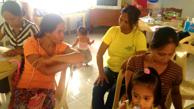 LEADER. Milagros Bendahon (in yellow shirt) listens to a community member during a workshop. Photo by Jodesz Gavilan