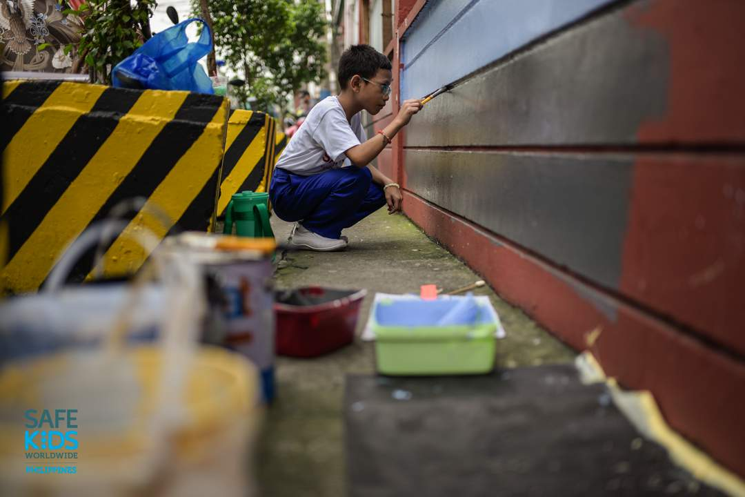 MURAL DESIGN. A student paints road safety-related art on the walls outside the school to raise more awareness for road users passing by the area. Photo by Heinz Reimann Orais