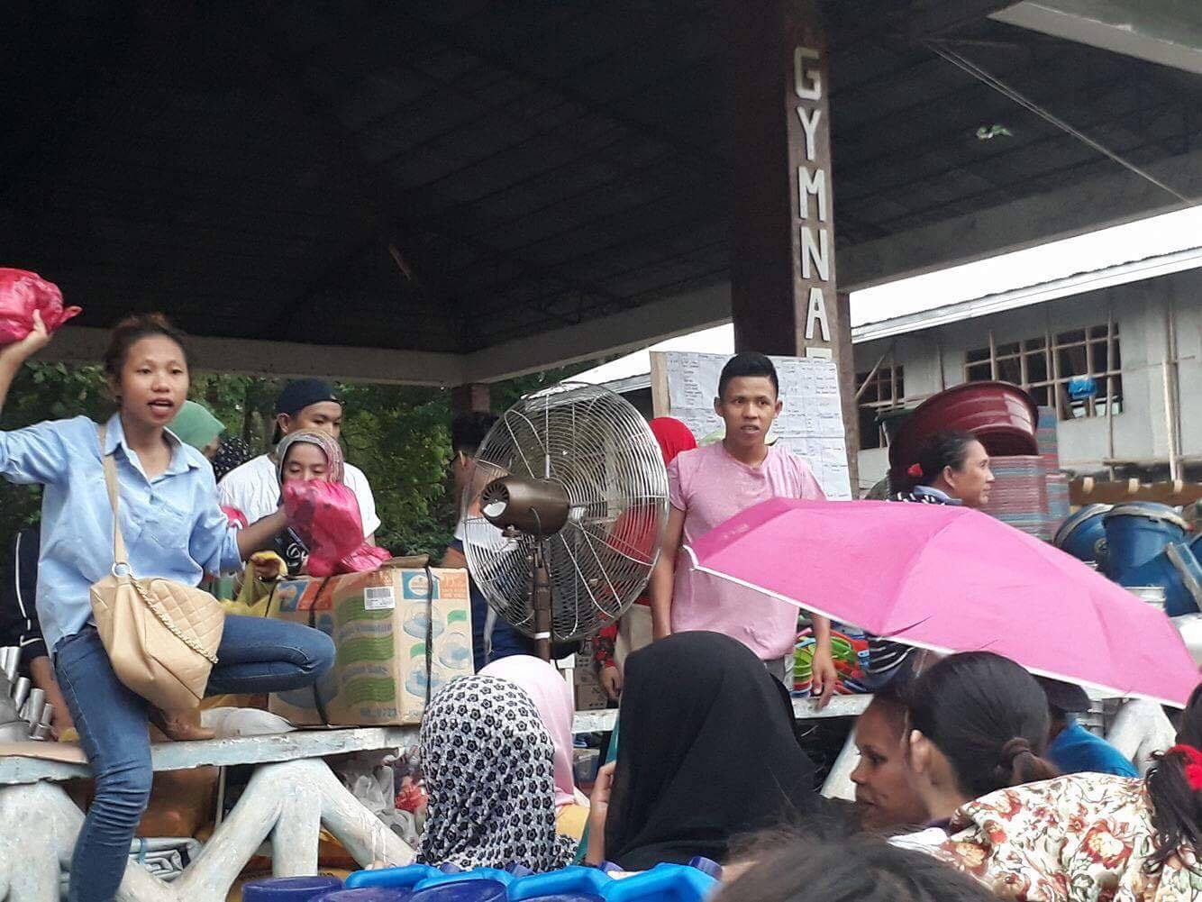 STUDENT VOLUNTEER. 18-year-old Najmah Asum (in blue) helps the local social welfare and development unit in distributing relief goods in Buru-un evacuation center in Iligan City. Photo courtesy of Najmah Asum